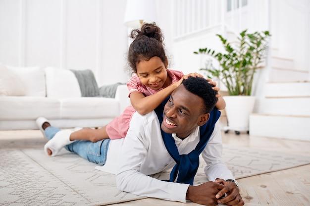 Père souriant et petite fille pose dans le salon. papa et enfant de sexe féminin s'amusent ensemble dans leur maison, relation heureuse