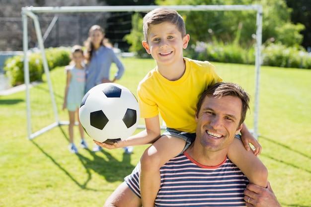 Père souriant portant son fils sur l'épaule au parc