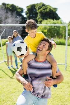 Père souriant portant son fils sur l'épaule
