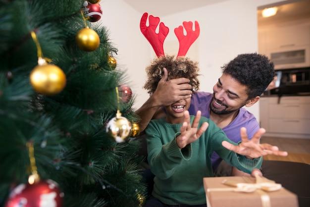 Père surprenant sa fille avec un cadeau par l'arbre de noël