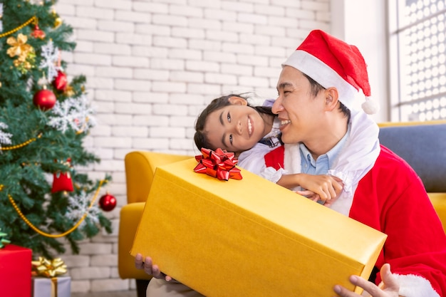 Le père surpris et a envoyé la boîte-cadeau à la petite fille le temps de joyeux noël.