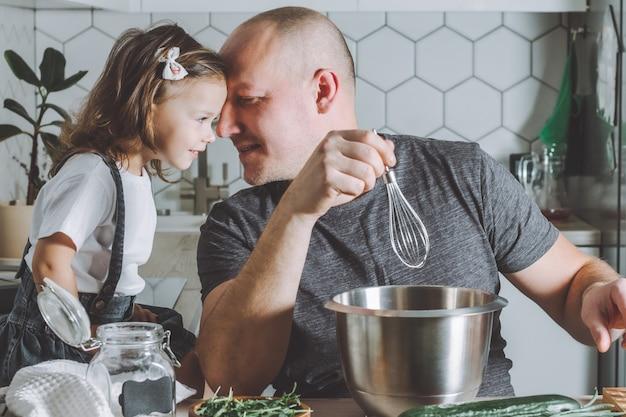 Père tenant un fouet, jouant avec sa fille. homme faisant les tâches ménagères.
