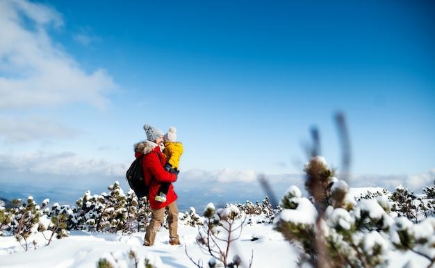 Père tenant un petit fils dans la neige dans la nature hivernale, concept de vacances en slovaquie. espace de copie.