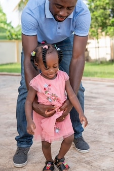 Père tenant sa fille en marchant