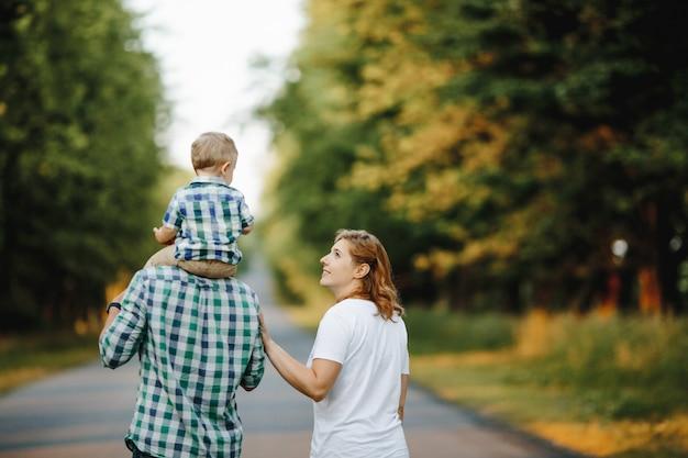 Père tient un fils sur leurs épaules, une mère est à proximité
