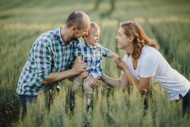 Le père tient un fils et une mère le garde pour les mains