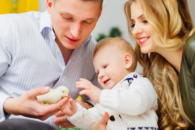 Père tient un petit poulet jaune et un petit garçon et sa maman le regardent et sourient