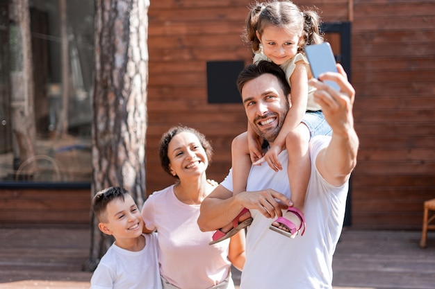 Un père tient sa fille sur ses épaules, tient un téléphone à la main et prend un selfie en famille avec sa femme et ses enfants, ils profitent des vacances d'été. sur fond de maison en bois.