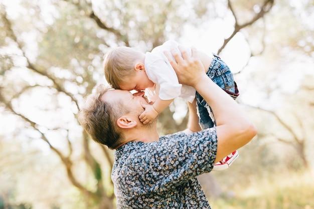 Le père tient son fils au-dessus de lui, ils se touchent le nez, le fils tient le père par la joue