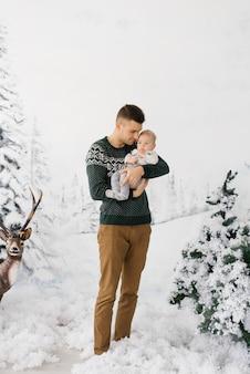 Un père tient son jeune fils dans ses bras dans la forêt d'hiver. paternité heureuse. vacances de noël et du nouvel an