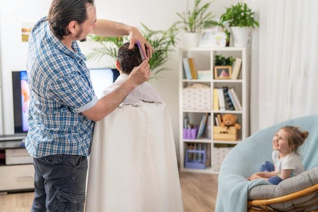 Le père tond son fils à la maison. la nécessité de mettre à jour les cheveux de l'enfant