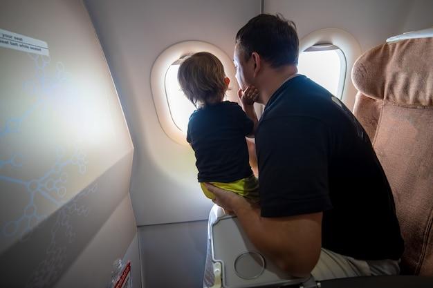 Père et tout-petit mignon assis dans un avion et regardant le ciel à travers le hublot. concept de premier vol, voyageant avec des enfants
