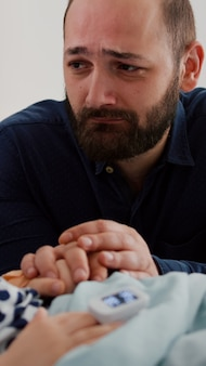 Un père triste et inquiet pleurant à côté d'une fille malade en attente de soins de santé lors d'une consultation de récupération médicale dans une salle d'hôpital. enfant endormi en convalescence après une opération de maladie