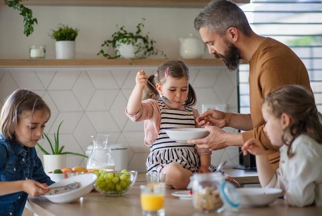 Un père avec trois filles à l'intérieur à la maison, prenant son petit déjeuner dans la cuisine.