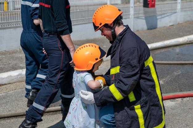 Le père en uniforme de feu enseigne à sa fille la formation de pompier