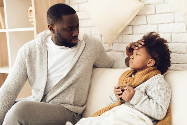 Le père vérifie la température de sa fille assise sur son lit.