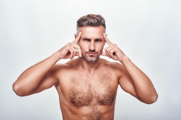 Perfection bel et sexy homme avec un chaume tenant la tête dans les mains et regardant