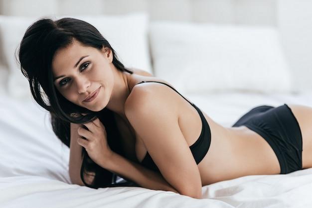 Perfection pure. jolie jeune femme en sous-vêtements noirs en regardant la caméra