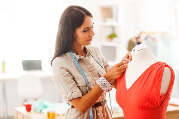 Perfectionner le style. belle jeune femme épinglant le textile sur la robe en se tenant debout dans son atelier de mode