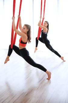 Performance d'étirement des jambes de groupe avec du lin rouge