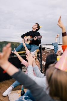 Performance live de musicien à la fête d'anniversaire. compagnie d'amis à loisir, guitariste confiant et ses fans