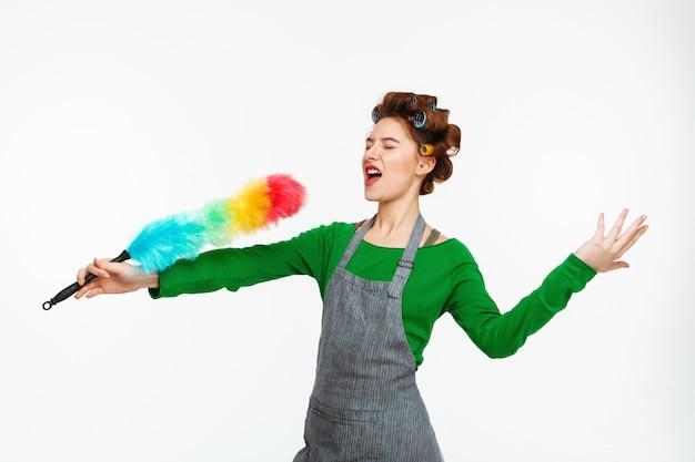 Performances drôles de belle femme tenant un plumeau et chantant