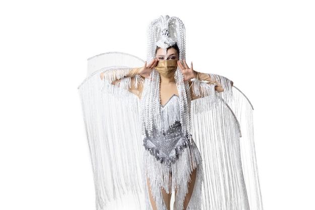 Performer. belle jeune femme en costume de mascarade de carnaval avec des plumes blanches dansant sur fond blanc. concept de célébration de vacances, temps de fête, danse, fête, bonheur. copyspace