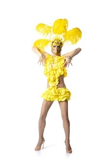 Performer. belle jeune femme en costume de mascarade de carnaval avec des plumes jaunes dansant sur fond blanc. concept de célébration de vacances, temps de fête, danse, fête, bonheur. copyspace