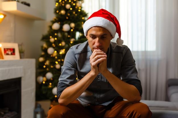 Période de noël. homme seul priant. mur de noël avec des lumières accrochées au sapin de noël. ambiance festive à la maison pendant l'hiver.