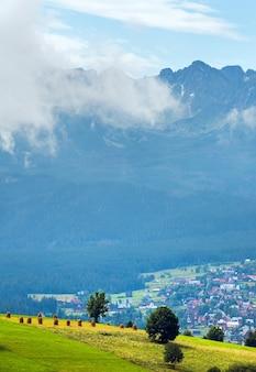 La périphérie du village de montagne brumeux d'été avec la chaîne des tatras (gliczarow gorny, pologne)