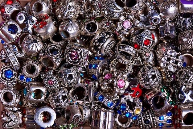 Perles en argent de différentes formes avec des pierres de couleur en gros plan.