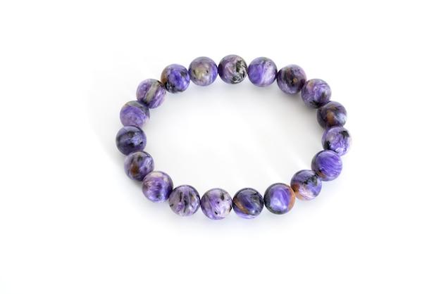 Perles charoïdes en bracelets sur fond blanc