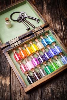 Perles colorées dans des mini bouteilles en verre rétro. ensemble fait à la main dans une boîte