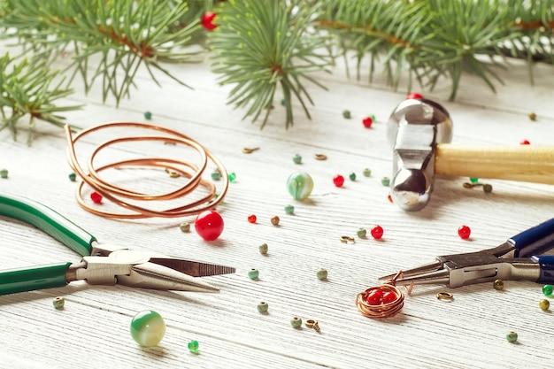 Perles colorées, fil de cuivre et outils de bijouterie. enroulement de fil. humeur de noël