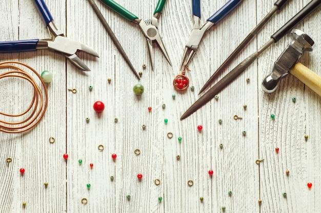 Perles colorées, fil de cuivre et outils de bijouterie. enroulement de fil. vue de dessus