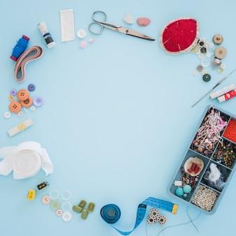Perles colorées; ruban; ciseaux; bouton et ruban à mesurer disposés en cercle avec espace pour l'écriture du texte