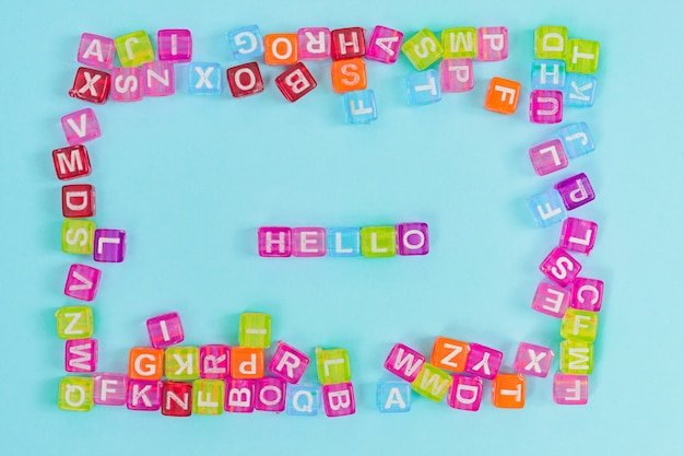 Perles de cube en plastique multicolore avec des lettres éparpillées sur fond bleu. texture de fond de l'alphabet anglais