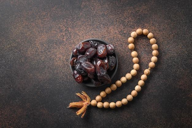 Perles et dates de prière en bois de ramadan dans la cuvette sur la tradition religieuse brune d'eid mubarak