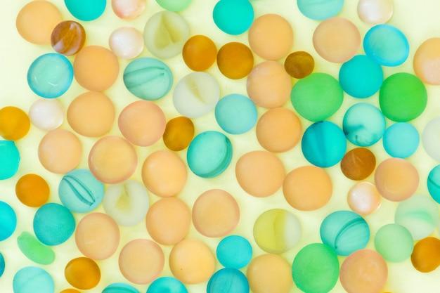 Perles, perles colorées sur une vue de dessus de fond blanc jaune