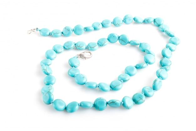 Perles de pierre semi-précieuses bleues isolées sur une surface blanche