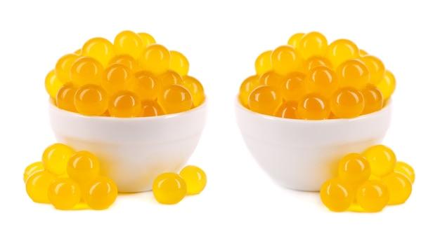 Perles de tapioca jaunes pour thé à bulles isolés sur fond blanc. perles de tapioca dans un bol en céramique.