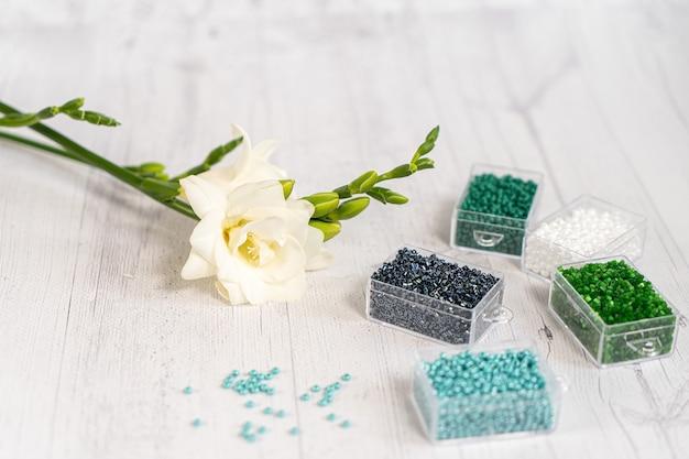 Perles de verre colorées avec des fleurs. variété de formes et de couleurs pour réaliser une perle ou un collier de perles pour femme