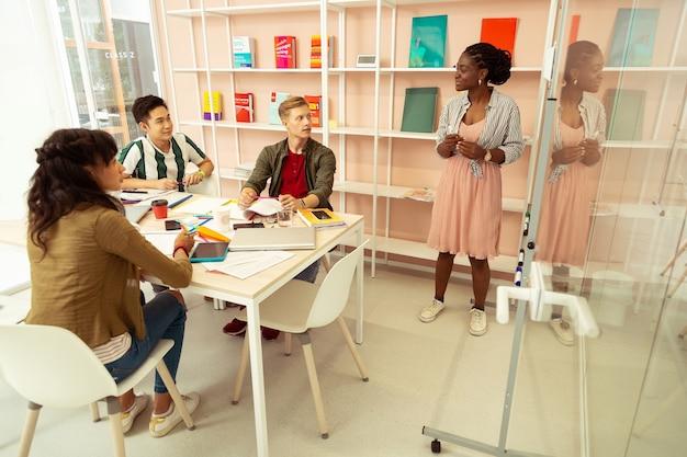 Permet de communiquer. homme blond attentif assis près de ses camarades de classe tout en écoutant son tuteur