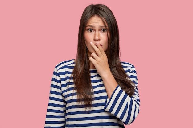 Perplexe fille inquiète garde les deux doigts sur les lèvres, a le regard frustré, essaie de trouver une solution