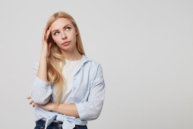 Perplexe jolie jeune femme blonde posant, redressant ses longs cheveux avec la main et regardant de côté avec perplexité