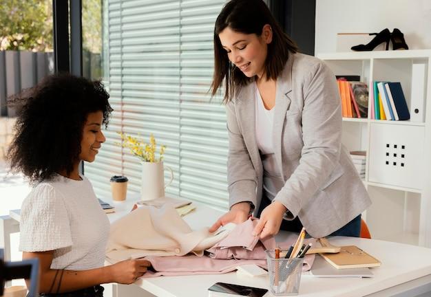 Personal shopper au bureau avec le client montrant un pantalon