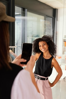 Personal shopper au bureau avec client prenant des photos