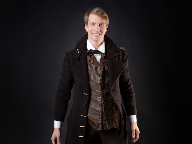 Personnage de l'histoire steampunk un jeune homme séduisant dans un long manteau élégant