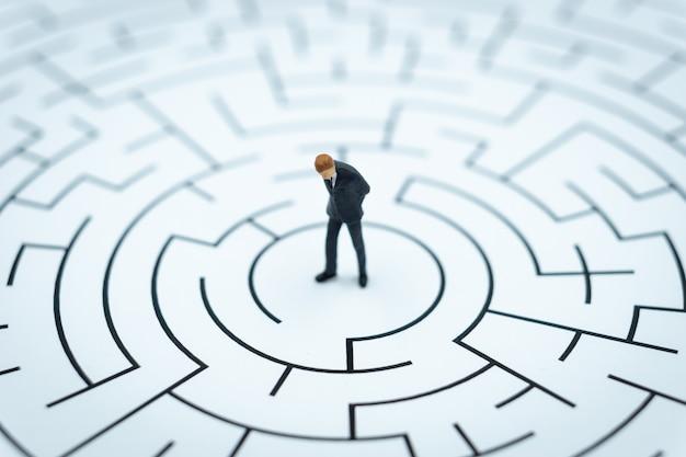 Personnage miniature homme d'affaires marcher dans un labyrinthe