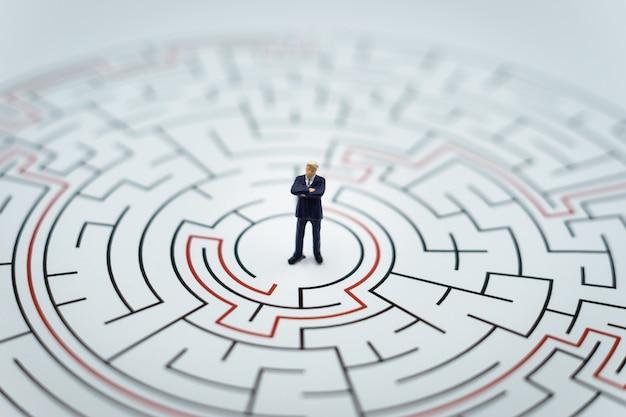 Personnage miniature homme d'affaires marcher dans un labyrinthe.